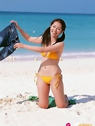 Energetic asian beauty playing on the beach in her bikini